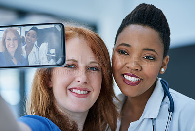 Buy stock photo Shot of two young doctors taking a selfie together