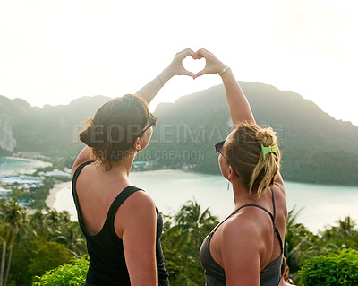 Buy stock photo Shot of two friends making a heart shape with their hands while on holiday in Thailand