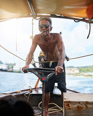 Buy stock photo Shot of a Thai man operating his tourist boat