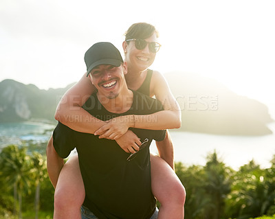 Buy stock photo Shot of a young man carrying his girlfriend on his back while holidaying together in Thailand