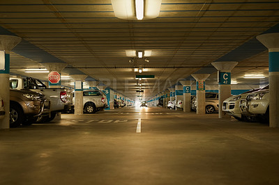 Buy stock photo Shot of an underground parking garage full of cars