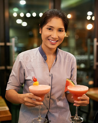 Buy stock photo Portrait of a friendly waitress carrying cocktails in a bar