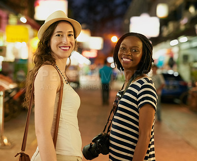 Buy stock photo Portrait of two happy young friends exploring a foreign city at night