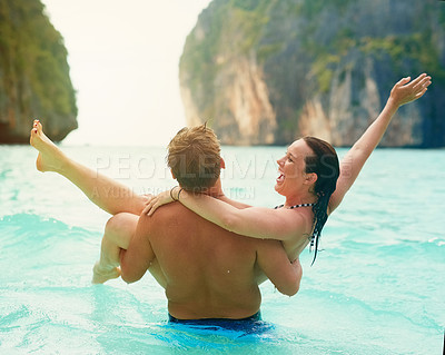 Buy stock photo Rearview shot of a man carrying his happy girlfriend into the sea
