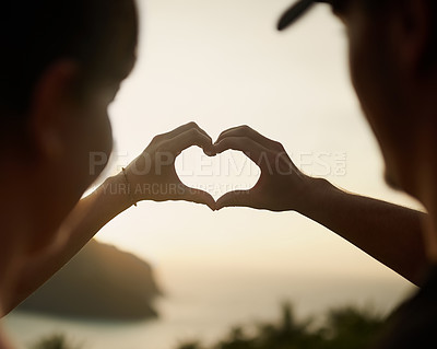Buy stock photo Rearview shot of a couple making a heart shape with their hands over a sunset landscape