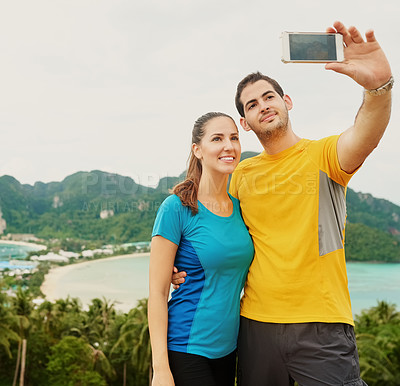 Buy stock photo Shot of a happy young couple taking a selfie on an island vacation