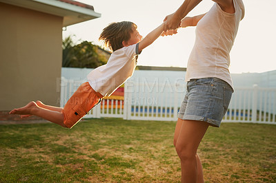 Buy stock photo Shot of a mother playfully swinging her son around in their backyard