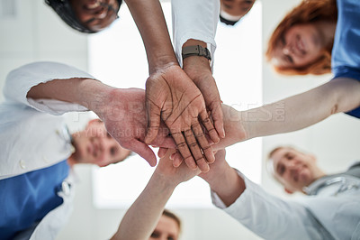 Buy stock photo Low angle shot of a group of medical practitioners joining their hands together in unity