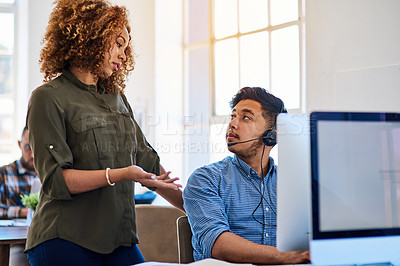 Buy stock photo Shot of a young phone operator speaking with a coworker at his desk