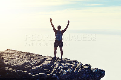 Buy stock photo Rearview shot of an unidentifiable young man raising his arms in triumph on a mountaintop