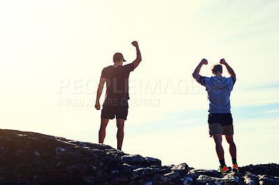Buy stock photo Rearview shot of two unidentifiable young men raising their arms in triumph on a mountaintop