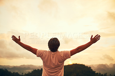 Buy stock photo Rear view shot of a young man standing outside with his arms outstretched