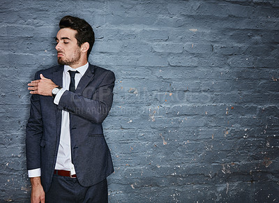 Buy stock photo Shot of a businessman brushing off his shoulders against a grey wall
