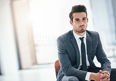 Buy stock photo Portrait of a serious young businessman posing in the office