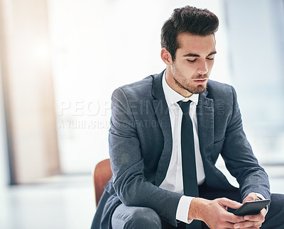 Buy stock photo Shot of a focussed young businessman using his smartphone in the office