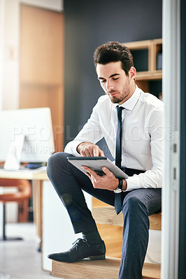 Buy stock photo Shot of a trendy young businessman using his tablet while sitting on the stairs in his office