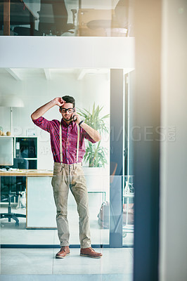 Buy stock photo Full length shot of a handsome young designer talking on his cellphone in the office