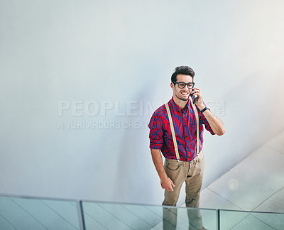 Buy stock photo High angle shot of a handsome young designer talking on his cellphone in the office