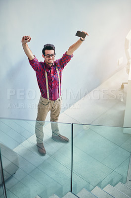 Buy stock photo High angle shot of a handsome young designer standing with his arms raised in the office