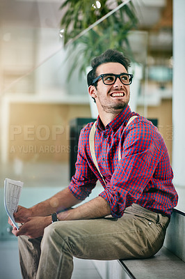 Buy stock photo Cropped shot of a handsome young designer holding paperwork in his office