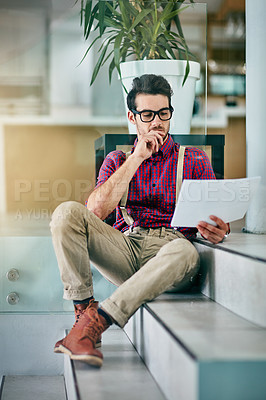 Buy stock photo Full length shot of a handsome young designer looking at paperwork in his office