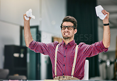 Buy stock photo Cropped shot of a frustrated young designer crumpling paper while sitting in his office