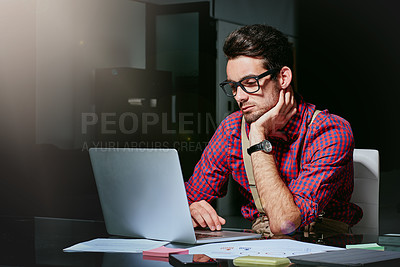 Buy stock photo Cropped shot of a handsome young designer working on his laptop in the office