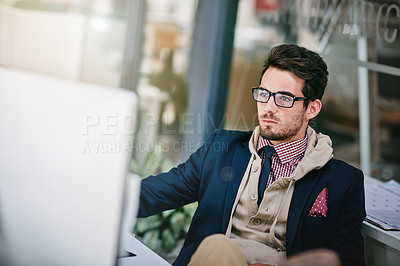 Buy stock photo Shot of a trendy young businessman sitting with his feet on the desk while using his computer
