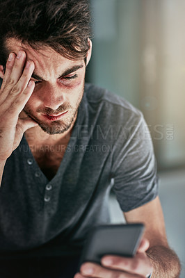 Buy stock photo Cropped shot of a beaten and bruised young man reading a text message