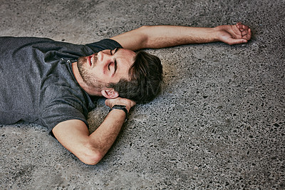 Buy stock photo High angle shot of a beaten and bruised young man passed out on the floor