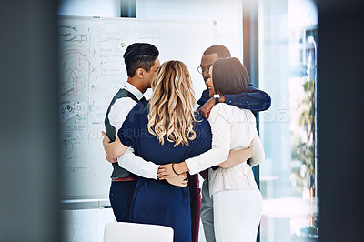 Buy stock photo Cropped shot of a group of businesspeople standing in a huddle in the office