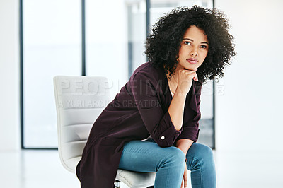Buy stock photo Portrait of a confident young woman sitting on a chair at work in a modern office