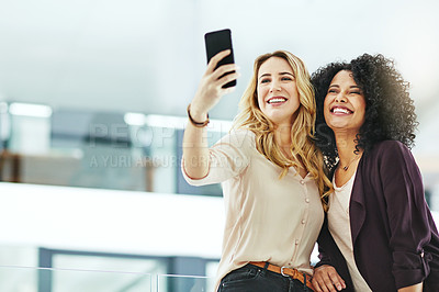 Buy stock photo Shot of two colleagues taking a selfie together on a phone at work