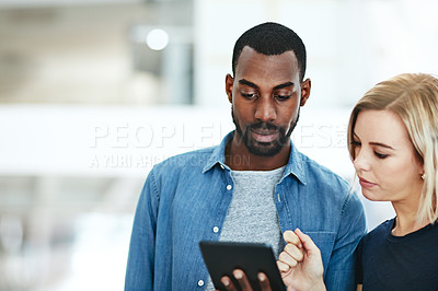 Buy stock photo Shot of two colleagues using a digital tablet together in a modern office