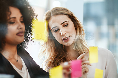 Buy stock photo Shot of two colleagues having a brainstorming session in a modern office