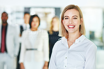 Buy stock photo Portrait of an ambitious young woman standing in a modern office with her colleagues in the background