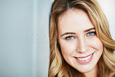 Buy stock photo Portrait of a beautiful young woman leaning against a wall