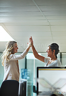 Buy stock photo Shot of two colleagues giving each other a high five at work