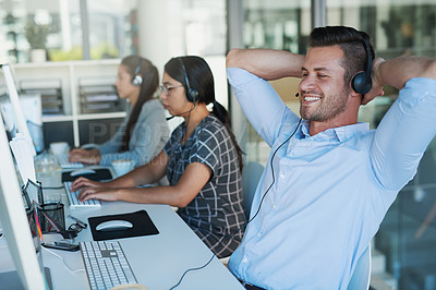 Buy stock photo Shot of a young man relaxing at his desk in a call center