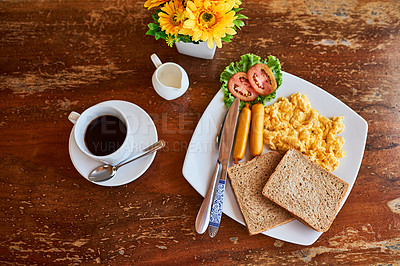 Buy stock photo High angle shot of a cup of coffee and freshly made breakfast on a table