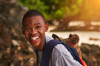 Buy stock photo Portrait of a happy young tourist exploring a tropical beach with a monkey on his backpack