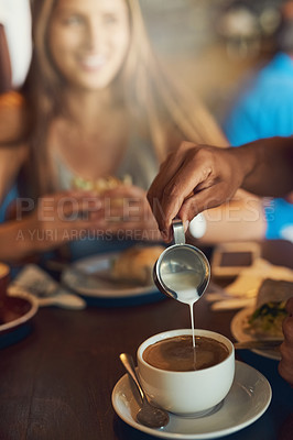Buy stock photo Closeup shot of a person pouring milk into their cup of coffee in a cafe