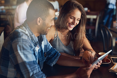 Buy stock photo Cropped shot of a young couple using a digital tablet while sitting in a cafe