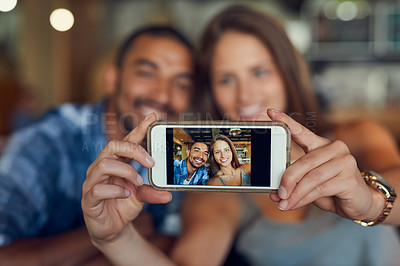 Buy stock photo Cropped shot of a young couple taking a selfie in a cafe
