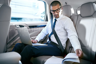 Buy stock photo Shot of a businessman working with his laptop and paperwork while sitting in a car