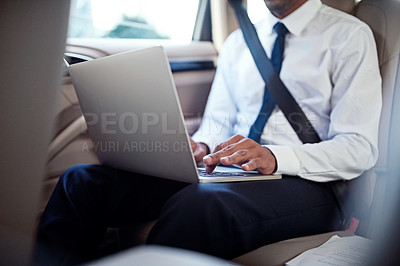 Buy stock photo Cropped shot of a businessman using a laptop in the back seat of a car