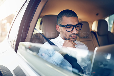 Buy stock photo Shot of a businessman using a laptop while sitting in his car