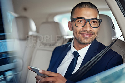 Buy stock photo Shot of a young businessman using his phone while riding in the backset of a car