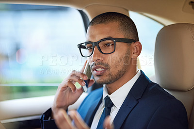 Buy stock photo Shot of a young businessman using his phone while riding in the back seat of a car