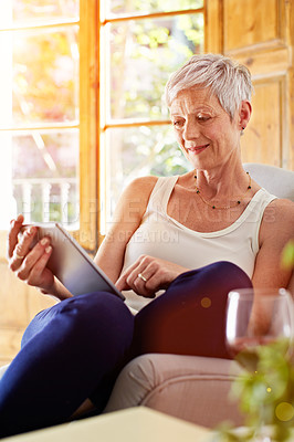Buy stock photo Shot of a mature woman relaxing on her sofa at home using a digital tablet
